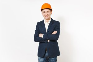 Young handsome successful smiling businessman in dark suit, protective construction helmet holding hands folded isolated on white background. Male worker for advertisement. Business, working concept.