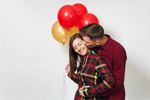 Beautiful caucasian young happy kissing couple in love. Woman and man in plaid checkered clothes with red, yellow balloons, celebrating birthday, on white background isolated. Holiday, party concept.
