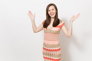 Beautiful young brunette female in light beige and pink patterned dress rejoices, smiling and spread hands with copy space in different directions in studio on white background. Concept of good mood