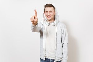 Young smiling man in t-shirt, light sweatshirt with hood, headphones touch something like click on button copy space or pointing at floating screen isolated on white background. Concept of emotions.