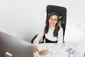 Beautiful smiling brown-hair business woman in suit and glasses sitting at the desk, working at computer with contemporary monitor with documents in light office, hands on keyboard on white background