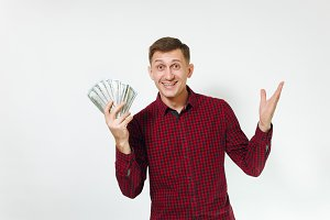 Handsome cheerful positive satisfied caucasian lucky young happy business man 25-30 years in red shirt holding wad of cash money on white background isolated for advertisement. Winner with dollars.