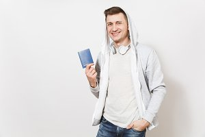 Young handsome smiling man student in t-shirt, light sweatshirt with hood, headphones holds international passport and shows it to the camera isolated on white background. Concept of travel, tourism