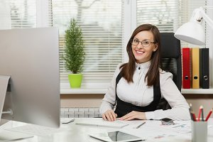 Beautiful smiling brown-hair business woman in suit and glasses sitting at the desk with tablet, working at computer with modern monitor with documents in light office, looking at the camera