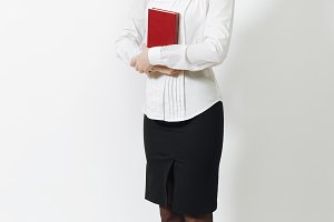 Full length of beautiful European young smiling brown-hair woman in white shirt, black skirt, glasses with red book isolated on white background. Manager, worker, student. Copy space for advertisement