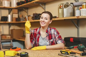 Beautiful smiling caucasian young brown-hair woman in plaid shirt, gray T-shirt, yellow gloves with spanner working in carpentry workshop at wooden table place with different tools. Gender equality.