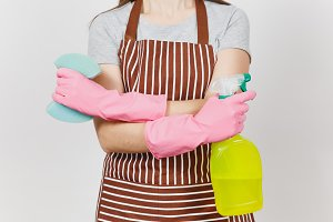 Close up cropped portrait housewife in pink gloves, striped apron isolated on white background. Woman holding hands crossed, spray bottle with cleaner liquid, sponge. Copy space for advertisement.
