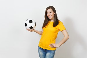 Beautiful European young cheerful happy woman, football fan or player in yellow uniform holding soccer ball isolated on white background. Sport, play football, health, healthy lifestyle concept.