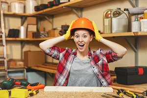 Young brown-hair woman in plaid shirt, gray T-shirt, yellow gloves, holding protective helmet with hands, working in carpentry workshop at wooden table place with piece of wood, different tools.