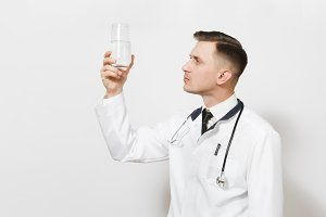 Pensive experienced handsome young doctor man isolated on white background. Male doctor in medical uniform, stethoscope looking on glass of clear water. Healthcare personnel, health, medicine concept.
