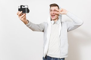 Young handsome smiling man student in t-shirt, light sweatshirt with hood, headphones photographs himself with victory sign on retro camera isolated on white background. Concept of photography, hobby