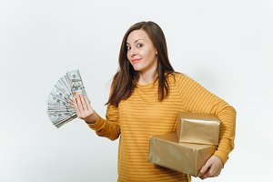Surprised sad dissatisfied young birthday woman in yellow clothes holding wad of cash money, golden gift boxes with present, celebrating holiday party on white background isolated for advertisement.