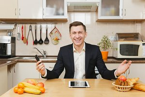 Handsome happy young business man in suit, shirt, having breakfast, sitting at table with tablet, spreading hands with mobile phone, eating fruits on light kitchen. Healthy lifestyle. Cooking at home.