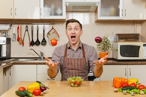 Fun crazy caucasian young man in apron, brown shirt sitting at table, throwing up onion and tomato, cuting vegetable salad with knife in light kitchen. Dieting concept. Cooking at home. Prepare food.