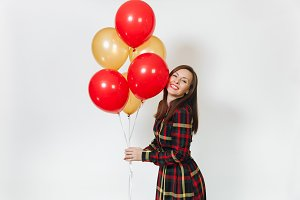 Beautiful caucasian young happy woman in long plaid checkered dress with shy charming smile, red, yellow golden balloons, celebrating birthday, on white background isolated. Holiday, party concept.