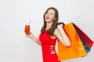Attractive glamour fashionable young woman in red dress holding glass of drink cocktail, multi colored packets with purchases after shopping isolated on white background. Copy space for advertisement.