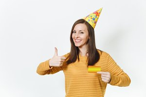 Beautiful caucasian lucky fun young happy woman in yellow clothes, birthday party hat holding golden credit card, celebrating holiday, showing thumb up on white background isolated for advertisement.