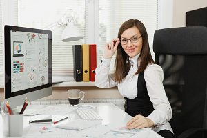 Beautiful smiling brown-hair business woman in suit and glasses sitting at the desk with cup of coffee, working at computer with modern monitor with documents in light office, looking at the camera