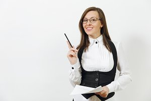 Beautiful smiling caucasian young brown-hair business woman in black suit, white shirt, glasses with work paper documents isolated on white background. Manager or worker. Copy space for advertisement.