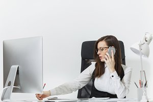 Beautiful serious business woman in suit and glasses sitting at the desk, working at contemporary computer with documents in light office, talking on mobile phone resolving issues, on white background