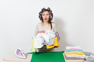 Distressed upset housewife with curlers on hair in light clothes holding basket of unshielded family clothing on ironing board with iron. Woman isolated on white background. Copy space advertisement.