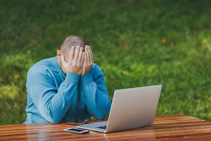 Upset angry shocked man businessman or student in casual blue shirt, glasses sit at table in city park use laptop work outdoors, cover face with hands, concerned about problems. Mobile Office concept.