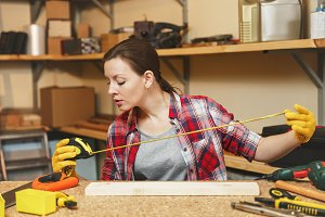 Beautiful caucasian young brown-hair woman in plaid shirt, gray T-shirt, yellow gloves working in carpentry workshop at wooden table place with different tools, measuring length of bar by tape measure