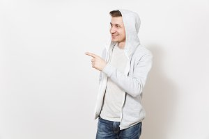 Young handsome smiling man student in t-shirt, blue jeans and light sweatshirt looking aside, pointing index finger aside on copy space isolated on white background. Concept of emotions, good mood.