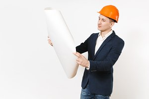 Young handsome pensive businessman in dark suit, protective construction orange helmet unrolling blueprint plan isolated on white background. Male worker for advertisement. Business, working concept.