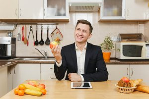 Handsome caucasian young business man in suit, shirt, having breakfast, sitting at table with tablet, eating apple on light kitchen. Dieting concept. Healthy lifestyle. Cooking food at home.