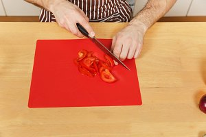 Man in apron sitting at table, cuts tomato and vegetables for salad with knife on red board in light kitchen. Dieting concept. Cooking at home. Prepare food. Top view. Copy space for advertisement.