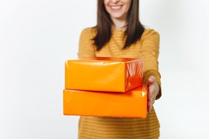 Close up caucasian fun young happy woman in yellow clothes, on birthday party holding orange gift boxes with present, celebrating and enjoying holiday on white background isolated for advertisement.