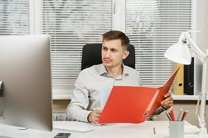 Handsome serious and engrossed business man in shirt sitting at the desk, working at computer with modern monitor, red folder, documents in light office on window background. Manager or worker.