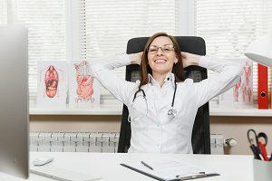 Young smiling happy female doctor sitting at desk in light office in hospital. Woman in medical gown, stethoscope relax rest with hands behind head in consulting room. Healthcare, medicine concept.