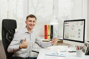 Handsome smiling business man in shirt sitting at the desk with lot of cash money, working at computer with modern monitor, lamp, documents in light office on window background. Manager or worker.