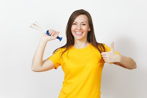 Beautiful European young happy brown-haired woman holding, blowing in football pipe, dressed in casual clothes, yellow t-shirt with shy charming smile isolated on white background. Sport fan concept.