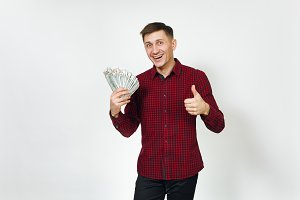 Handsome satisfied caucasian lucky young happy business man 25-30 years in red shirt holding wad of cash money, showing thumb up on white background isolated for advertisement. Winner with dollars.