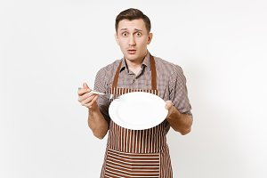 Man chef or waiter in striped brown apron, shirt holding white round empty clear plate, fork isolated on white background. Male housekeeper or houseworker. Domestic worker copy space for advertisement
