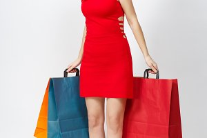 Full length of attractive glamour caucasian young brown-hair woman in red dress holding multi colored packets with purchases after shopping isolated on white background. Copy space for advertisement.