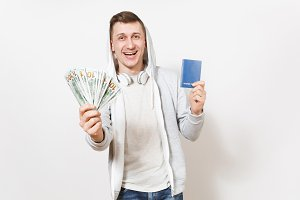 Young handsome smiling man in t-shirt, light sweatshirt with hood with headphones holds international passport, bundle of dollars, cash money isolated on white background. Concept of travel, tourism.