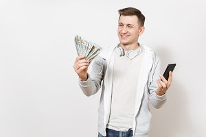 Young handsome smiling man in t-shirt and light sweatshirt with headphones around neck holds bundle of dollars, cash money and mobile phone in hands isolated on white background. Concept of success
