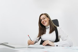 Beautiful smiling brown-hair business woman in suit and glasses sitting at the desk, working at computer with modern monitor and documents in light office, writing in notebook on white background
