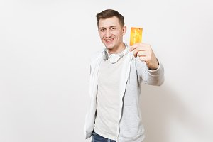 Young handsome smiling man student in t-shirt, light sweatshirt with headphones around neck holds orange credit card with money and shows it to camera isolated on white background. Concept of success