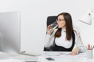 Beautiful smiling brown-hair business woman in suit and glasses sitting at the desk, drinking pure water, working at computer with modern monitor with documents in light office on white background
