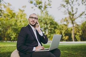 Young businessman in white shirt, classic suit, glasses. Man sit on soft pouf, work on laptop pc computer, talk on mobile phone in city park on green lawn outdoors. Mobile Office, business concept.