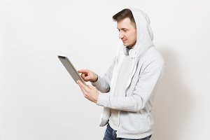 Young handsome man student in t-shirt and light sweatshirt with hood with headphones holds tablet pc computer in hands and using it isolated on white background. Concept of technology