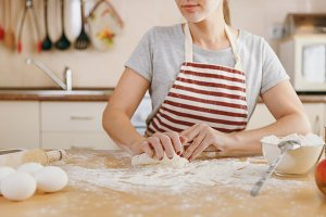 A young beautiful happy woman sitting at a table with flour, kneading dough and going to prepare a Christmas cakes in the kitchen. Cooking home. Prepare food close up.