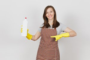 Young smiling housewife in yellow gloves, striped apron isolated on white background. Woman holding and pointing index finger on bottle with cleaner liquid for cleaning. Copy space for advertisement.