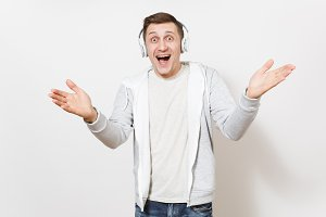 Young handsome smiling man student in t-shirt and light sweatshirt listening to music with white wireless headphones and spreads his hands in surprise isolated on white background. Concept of emotions