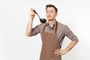 Young smiling man chef or waiter in striped brown apron, shirt tasting from black ladle or kitchen spoon isolated on white background. Male housekeeper or houseworker. Kitchenware and cuisine concept.